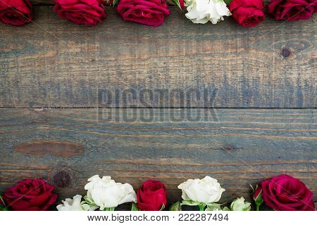 Floral frame of red and white roses on rustic wood background. Flat lay, top view. Floral background.