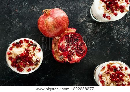 Top view on delicious healthy home-made desset from muesli, yoghurt and pomegranate on dark wooden background