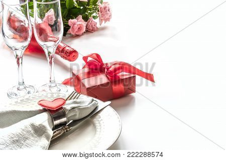Valentines day dinner with table place setting with red gift, glass for champagne, heart ornaments with silverware on white background. Close up. Valentine's card.