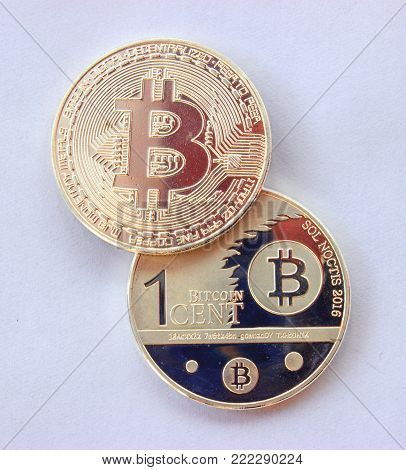 On a gray background are gold coins of a digital crypto  currency - one cent of bitcoin and bitcoin.