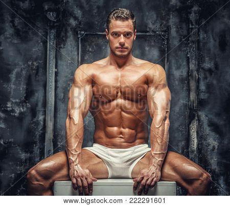 Awesome shirtles muscular guy sitting on white podium. Isolated on grey background.