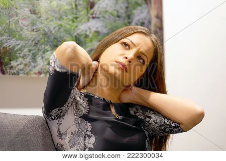 Tired neck. Brunette young woman suffering from neck pain at home on couch. A woman's sense of fatigue, exhausted, stressed. A girl massages her painful neck with her hands. The concept of body and health.