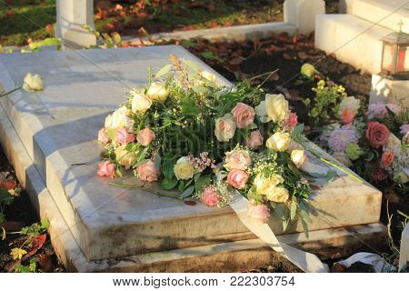 White and pink funeral flowers on a marble tomb