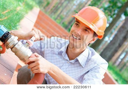 Smiling manual worker repairing a pipe