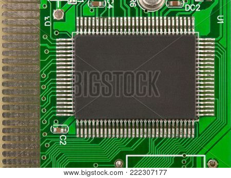 Big chip on the green PCB. There are a lot of legs of this chip, resistors and other small electronic elements here too.