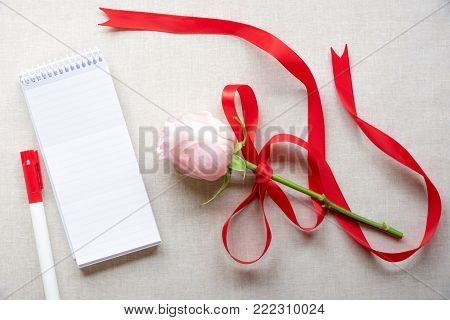 Blank notebook and a rose with red ribbon - Beautiful pink rose tied with red satin ribbon with bow, an unwritten spiral notebook with stripes and a marker pen, on a vintage fabric background.