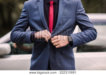 Successful business man in a dark business suit with a red tie against the background of a car. Stylish business man in a dark suit. Business professions. Business concept. Business vision. Successful business man in a classic suitFashionable watch on han