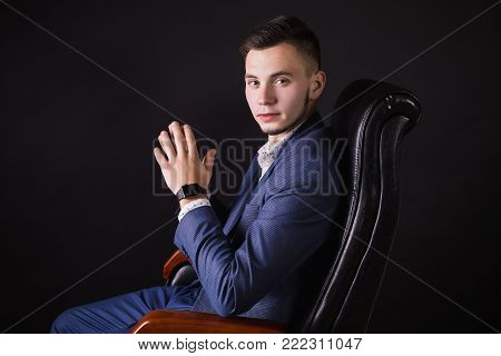 Interesting photo with people. Successful young business people with a business suit  on a dark background. Conceptual photography with people. An unusual image of people. Young people in the picture. Stylish man. Director of the firm.