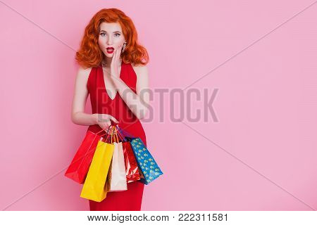 Girl in red dress with shopping bags on pink background. Black Friday shopping. A girl loves shopping. Shopping concept on a pink background. Stylish model with shopping bags. Do shopping on a black Friday