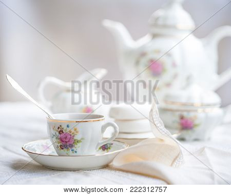 Luxury porcelain tea set with a cup, teapot, sugar bowl on white tablecloth with white bagels on a plate
