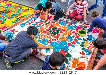 Antigua, Guatemala -  April 14, 2017: Children decorate dyed sawdust Good Friday procession carpet in town with most famous Holy Week celebrations in Latin America