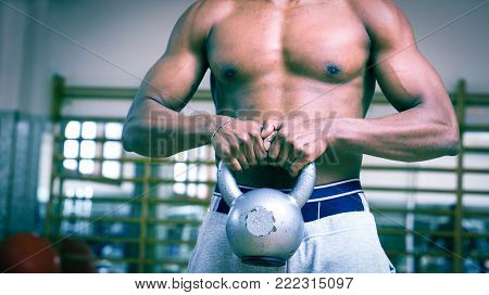 African american man inside gym lifting up kettlebell - Black body builder doing functional training basic exercise - Main focus on hands with dark blue filter look