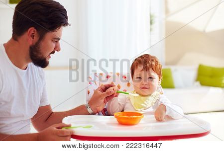 Father Teaches Son, Baby To Hold The Spoon And Eat By His Own