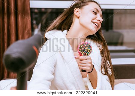 sweet funny girl dries her long hair with a hair dryer, sings in a comb poster