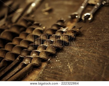 Old Rusty Drill Bits and Wrenches on Work Bench in Garage