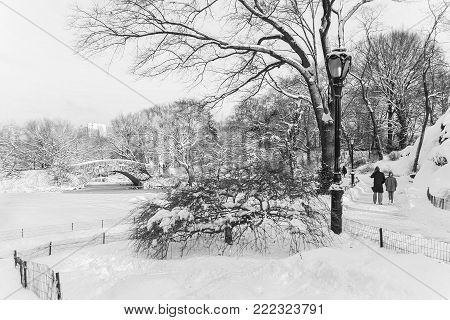 The snow filled landscape near the duck pond and stone bridge in Central Park.