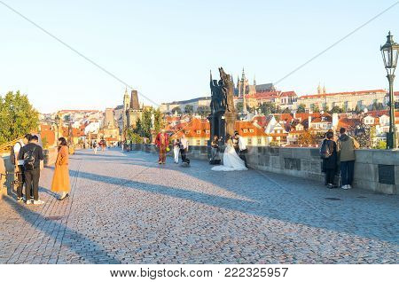 PRAGUE CZECH REPUBLIC - AUGUST 29,2017;  Charles Bridge at sunrise a few tourists and wedding group arrive to photgraph the historic area.