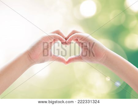 Heart-shape hand gesture of kid's body language for children's love, peace, kindness and world humanitarian aid concept. Hand isolated on sky with green bokeh and sun flare