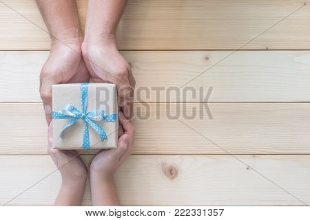 Father's day gift with daughter or son holding dad's hands giving present box with blue  ribbon on wood background to tell I love you dad and happy fathers day