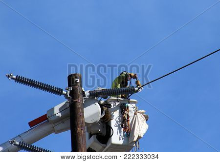 Culver City, California, 1/27/2018-Electrician construction worker drills electric wire from crane to restore power after strong winds.