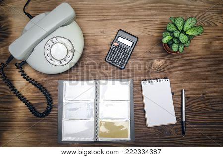 Contact us. Business conversation concept. Phone, business card holder with copy space and notebook on office workspace table.