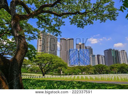 Manila, Philippines - Apr 14, 2017. Manila American Cemetery and Memorial with cityscape. The cemetery, 152 acres (62 ha) or 615,000 square metres in area, is located on a prominent plateau.