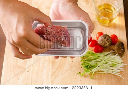 Chef's hand put raw pork mixed with spices and vegetables in small baking tray and roast pork cooking
