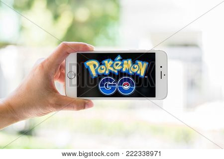 BANGKOK, THAILAND - January 18, 2018: Iphone smart phone gadget on hand with screen showing application Pokemon Go mobile gps game app developed by Niantic for iOS and Android devices
