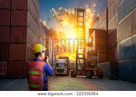dock worker control, Forklift handling container box loading and Container Cargo freight ship with working crane bridge in shipyard at sunrise for Logistic Import Export background