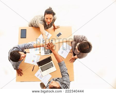Top view of businessmen and businesswoman standing and high five hands over table in a meeting with copy space on isolated white background in mobile office. Teamwork, diversity, success concept