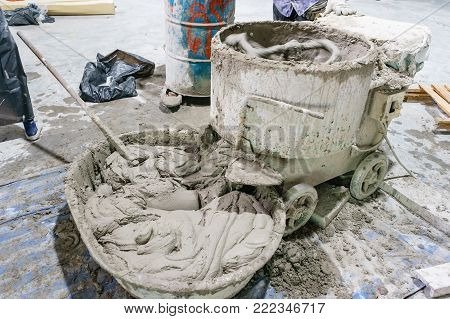 Cement or mortar is inside cement mixer. Cement or mortar is mixed on a construction site in an old electric cement mixer  for pouring concrete onto a tray