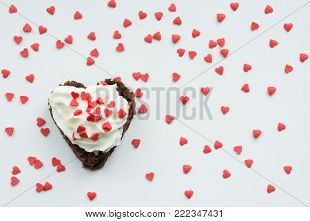 Valentine's card. Sweet cookies with cream topping and red heart for decor on white.