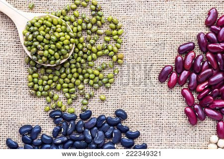 Many types of beans are separated in a spoon on a sackcloth. green bean, soybean, black bean, and red bean
