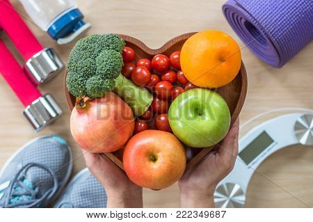 Healthy lifestyle concept, clean food good health dietary in heart dish with sporty gym aerobic body exercise workout training class equipment, weight scale and sports shoes in fitness center