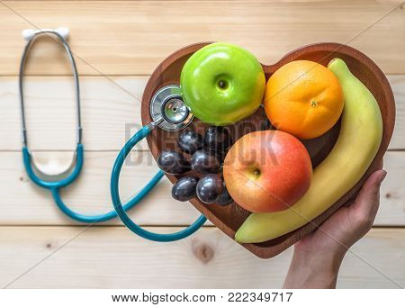 Cholesterol diet, diabetes control and healthy food nutritional concept with clean fruits in heart dish with cardiologist and nutritionist monitoring conceptual idea