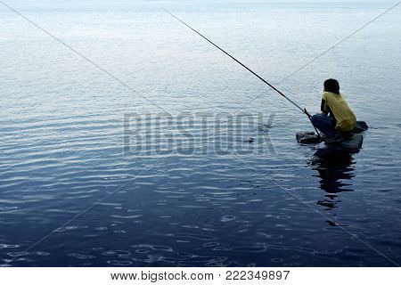 Fisher over blue water background, Fishing Boy