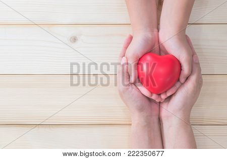 I love you Mom, Mother's Day celebration with woman holds young kid's hands supporting red heart gift, and charity donation for nursing children concept