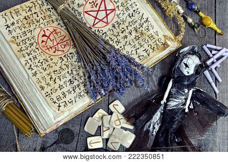 Witch book with magic symbols, lavender bunch, scary doll and runes on planks. Occult, esoteric, divination and wicca concept. No foreign text, all symbols on pages are fantasy, imaginary ones poster