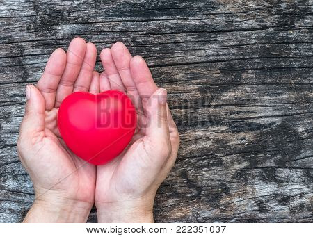 Red love heart on woman's hand support on aging old wood for promoting for health care campaign concept