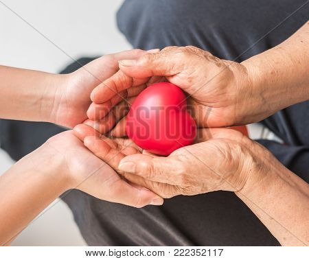 Elderly senior person or grand parent's hands with red heart  in support of nursing family caregiver for disability awareness day concept