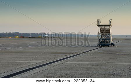 Lone airplane stairs on the tarmac at airport with airplane in background taxiing - solitude theme of missing the flight