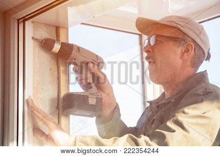 Carpenter in glasses working with a drill.