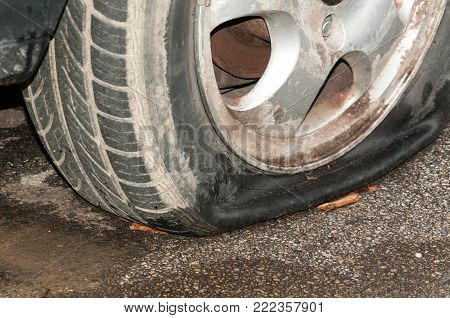 Flat tire. Flat car tire on the aluminum wheel close up with selective focus