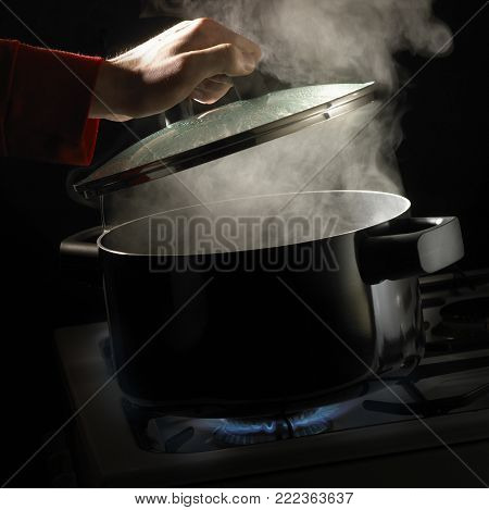 HAND LIFTING LID OFF PAN OF BOILING WATER AND RISING STEAM SIMMERING ON GAS COOKER