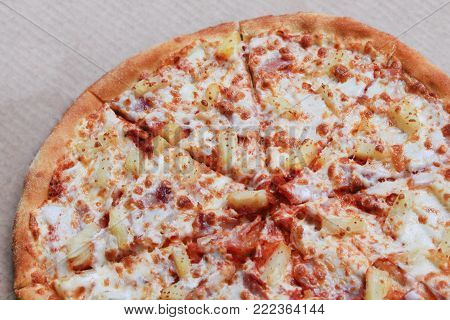 Pineapple Pizza or Hawaiian Pizza with Cheese, Pineapple, Tomato Original Sauce, Bacon or Ham Toppings. Close Up View of Freshly Cooked Tasty Pizza Pie on Thin Dough with Chunks in Delivery Box.