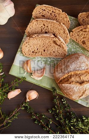 Composition of garlic and bread on a dark wooden table. Bread is cut into slices and a whole loaf is not far. Freshly baked hand-made bread on a kitchen towel.