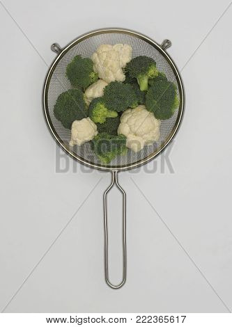 STAINLESS STEEL SIEVE CONTAINING FRESH CAULIFLOWER AND BROCCOLI FLORETS