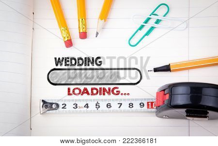Wedding Planner Notebook. pencils, pen and tape measure on a paper background.