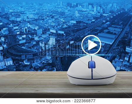 Play button with wireless computer mouse on wooden table over city tower, street and expressway, Business music online concept