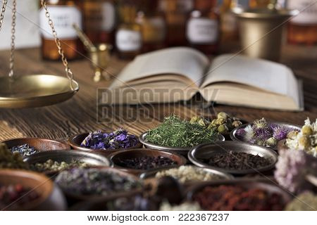 Alternative medicine. Herbs in bowls on wooden rustic table.